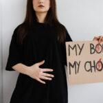 """Frau in schwarzem Kleid, die sich den Bauch hält und daneben ein Schild mit der Aufschrift """"My body, my choice"""" hält"""